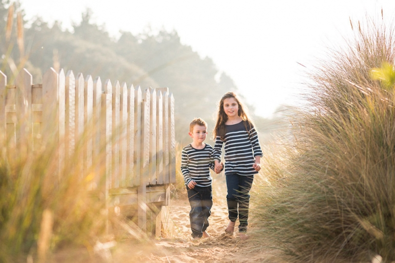 BROTHER AND SISTER IN LOW WINTER SUN SAND DUNES NORFOLK