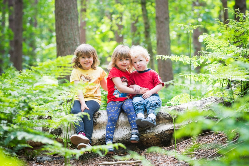 KIDS SITTING ON A LOG PORTRAIT IN WOODLAND