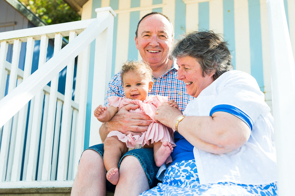 GRANDPARENTS AND GRAND DAUGHTER SITTING ON BEACH HUT STEPS