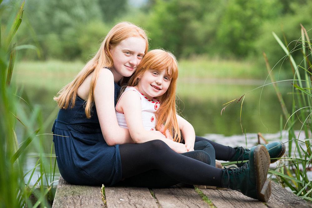 SISTERS SITTING BESIDE LAKE