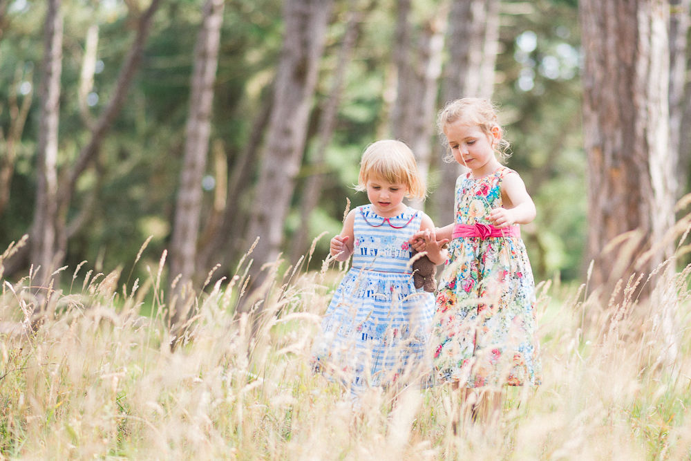 SISTERS EXPLORING THE LONG GRASS IN THE WOODS PHOTOGRAPH