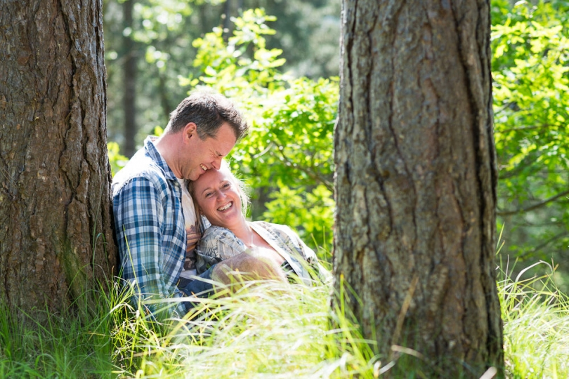 CUDDLING COUPLE IN THE WOODS AT THE BEACH