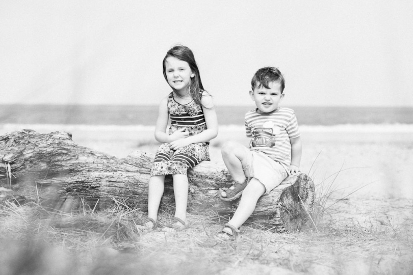 BROTHER AND SISTER BLACK AND WHITE PORTRAIT SITTING ON A LOG