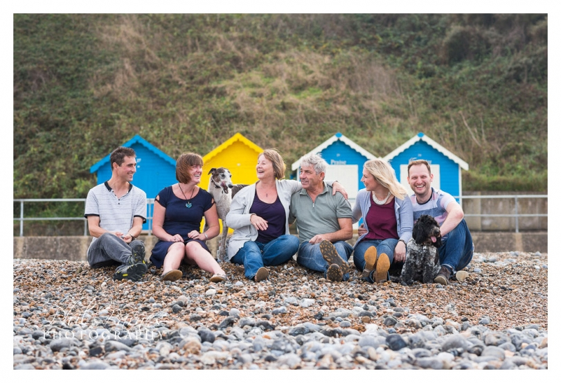 FAMILY SAT ON BEACH IN FRONT OF BEACH HUTS
