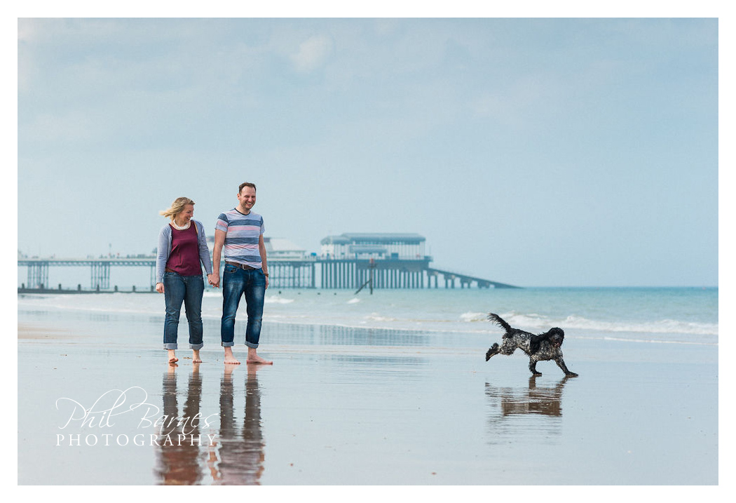 COUPLE AND THEIR DOG ON BEACH CROMER